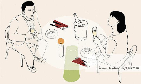 Paar trinkt Sekt am Tisch bei Kerzenschein