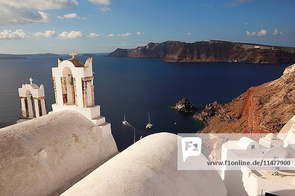 View to the bell tower of a white church at the cliff in Oia village with the Caldera at the background  Santorini  Cyclades Islands  Greek Islands  Greece  Europe.