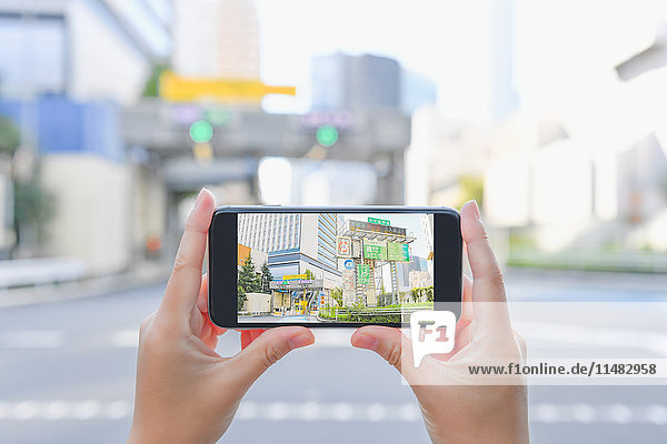 Japanese woman using augumented reality app on smartphone downtown Tokyo  Japan