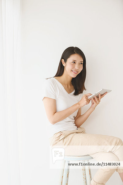 Young Japanese woman on a chair in a white room