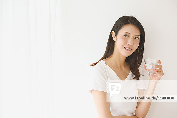 Portrait of young Japanese woman in a white room