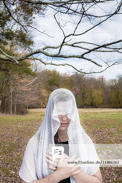 Young woman  standing in an open field  wearing a veil over her head.