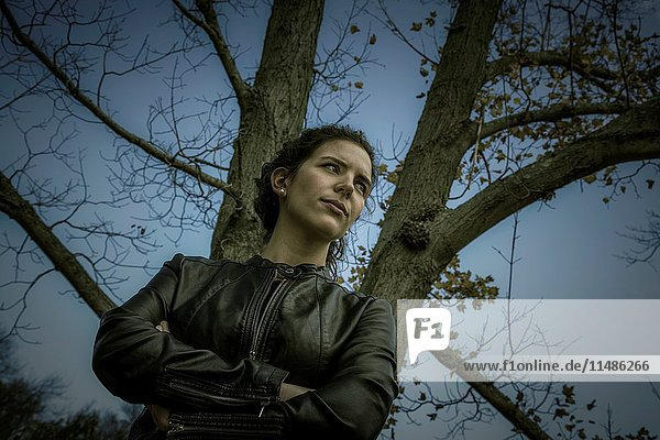 Young woman in a leather jacket standing next to a tree with no leaves.