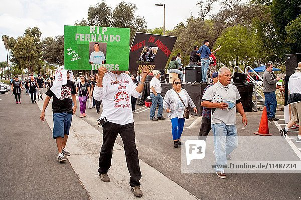 Carrying photos of dead violence victims  local Hispanics march in Santa Ana  CA  city park at a rally against street violence in the community. Note sign and T shirts with logo.
