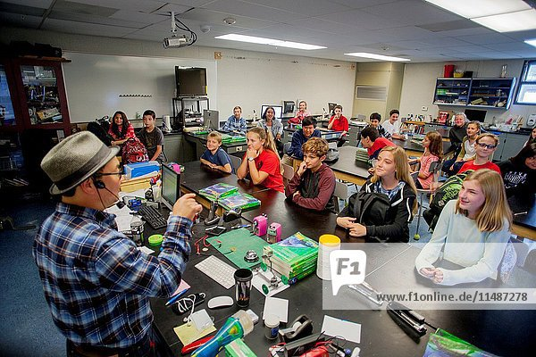 An Asian American science teacher lectures an attentive middle school STEM (Science  Technology  Engineering and Math) class in Mission Viejo  CA.