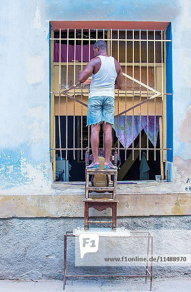 A Cuban man painting bars in old Havana street. The historic center of Havana is UNESCO World Heritage Site since 1982.