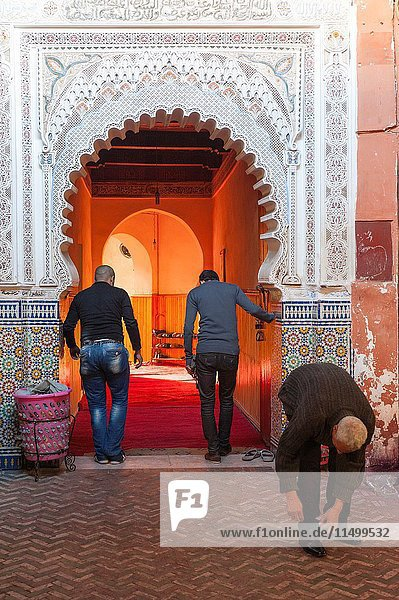 Marrakech  Morocco. Men taking off their shoes at the entrance of a mosque.