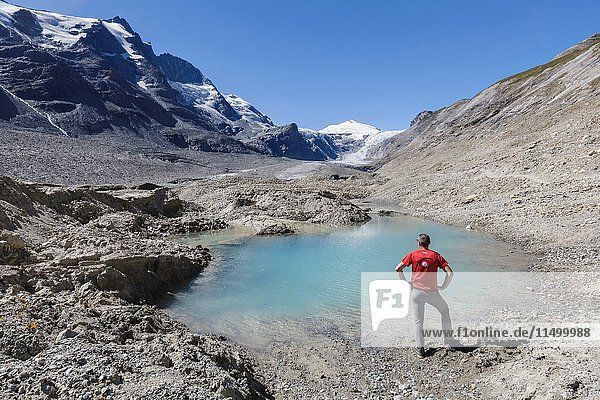 Europe  Austria  Carinthia  Glockner Group  High Tauern. A man lookin to Johannisberg mountain near a water pond on the Pasterze glacier at Grossglockner.