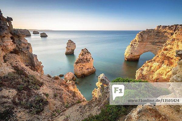 Sunrise on the cliffs and turquoise water of the ocean Praia da Marinha Caramujeira Lagoa Municipality Algarve Portugal Europe.