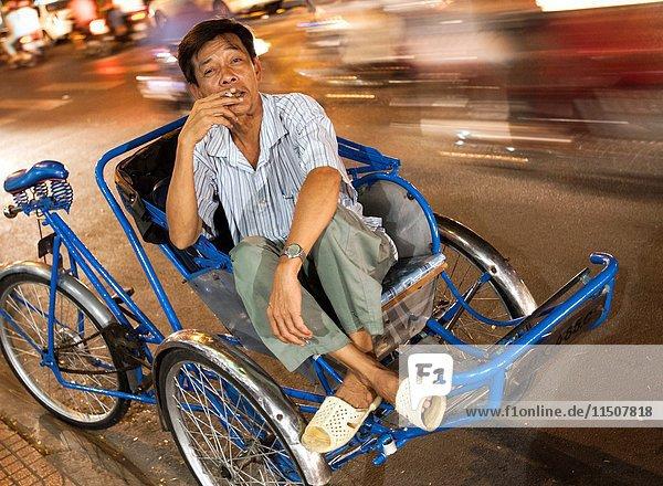 Rickshaw operator waits for customers Ho Chi Minh City Vietnam.