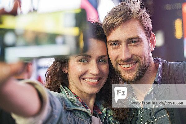 Junges Paar  das sich in der beleuchteten Stadtstraße selbstständig macht.
