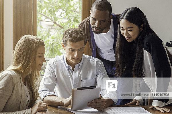 Kollegen schauen sich gemeinsam das digitale Tablett an