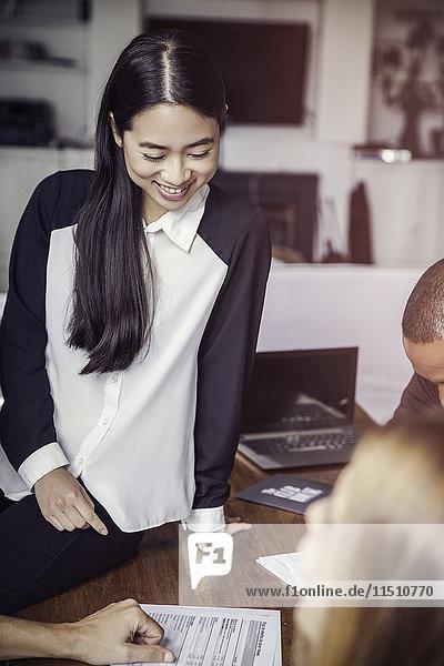 Junge Geschäftsfrau lächelt in lockerer Runde