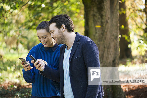 Couple using smartphones while walking in woods