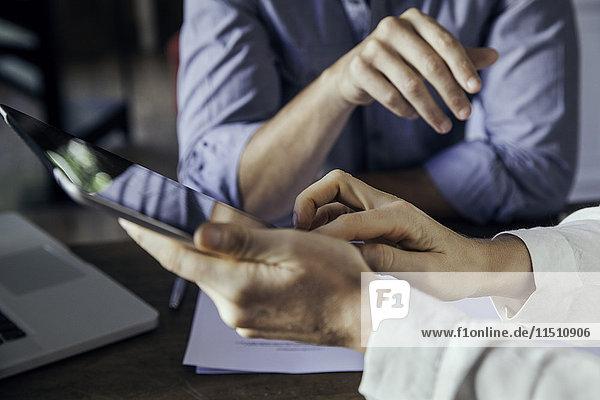 Kollegen  die sich gemeinsam ein digitales Tablett anschauen  beschnitten