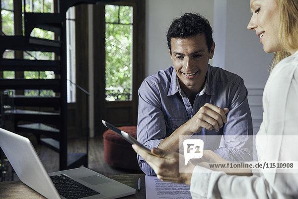 Geschäftsfreunde  die sich das digitale Tablett in ungezwungenen Meetings anschauen