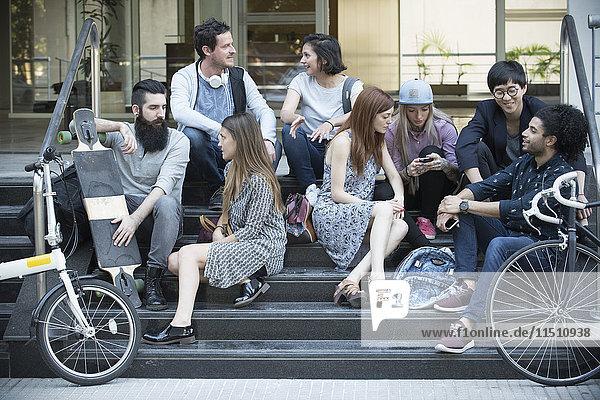 Gruppe von Freunden  die sich auf einer Treppe außerhalb des Gebäudes aufhalten.