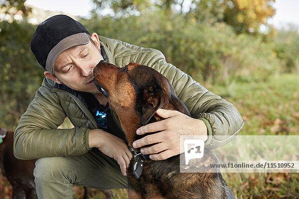 Hundeausführer  der sich bückt  um einen Hund zu streicheln  der an seinem Gesicht kuschelt.