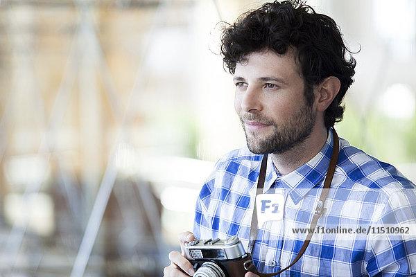 Mann hält Kamera und lächelt
