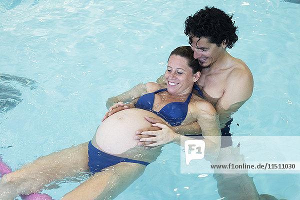 Schwangere Frau  die mit Hilfe eines Partners im Schwimmbad trainiert.