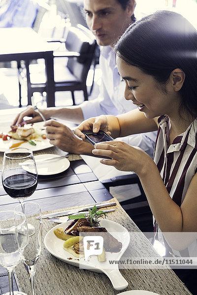 Frau fotografiert mit dem Smartphone ihr Essen im Restaurant
