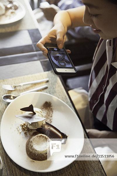 Frau fotografiert mit dem Smartphone Gourmet-Dessert im Restaurant