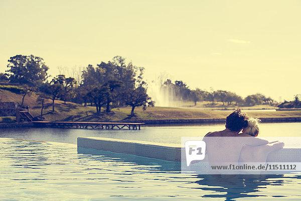 Paar Entspannung im Infinity-Pool mit Blick auf den See