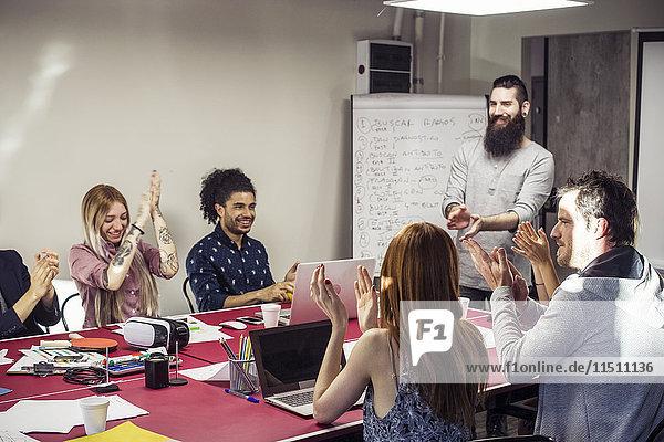 Geschäftsleute applaudieren beim Treffen