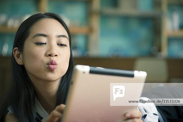 Junge Frau bläst Kuss während Videokonferenz auf digitalem Tablett