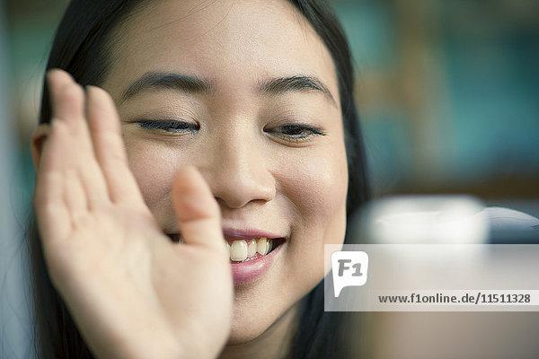 Junge Frau winkte vor der Kamera während einer Videokonferenz auf einem digitalen Tablett.