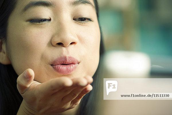 Junge Frau bläst Kuss vor der Kamera während einer Videokonferenz