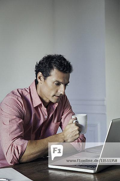 Mann  der Kaffee trinkt  während er den Laptop benutzt.