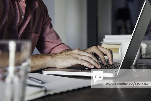 Mann tippt auf Laptop-Computer  beschnitten