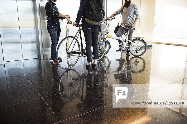 Männer warten auf Aufzug mit Fahrrädern und Longboard  niedrige Sektion