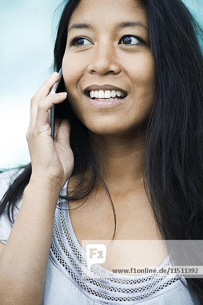 Frau spricht am Handy und lächelt