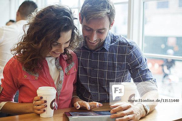 Paar mit digitalem Tablett im Coffee-Shop