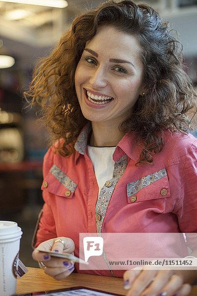 Frau beim Einkauf mit Kreditkarte  lächelnd  Portrait