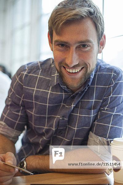 Mann sitzt im Café mit Kreditkarte in der Hand und lächelt fröhlich.