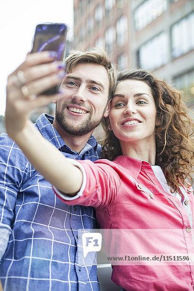 Ein Paar nimmt einen Selfie mit nach draußen.