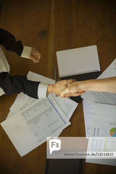 Geschäftsfrauen schütteln sich während des Treffens die Hand