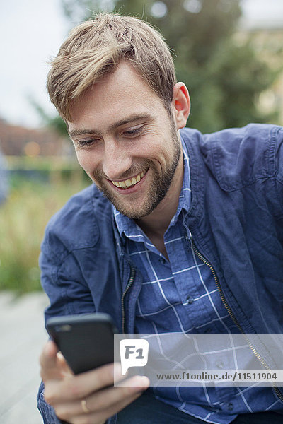 Young man text messaging with smartphone outdoors