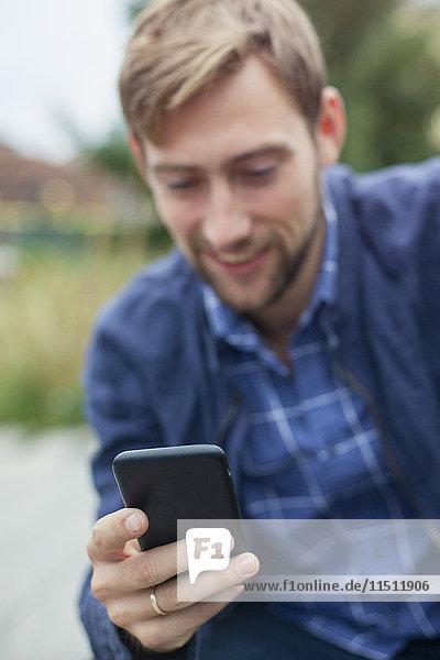 Mann mit Smartphone im Freien