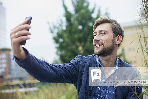 Junger Mann benutzt Smartphone  um einen Selfie nach draußen zu bringen.