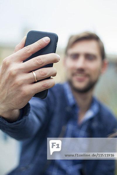 Mann  der ein Smartphone benutzt  um einen Selfie zu nehmen.