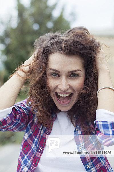 Unbeschwerte junge Frau lacht im Freien  Porträt