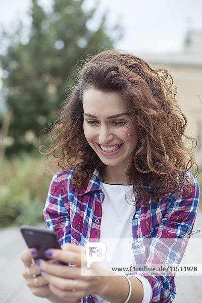 Fröhliche junge Frau mit Smartphone im Freien