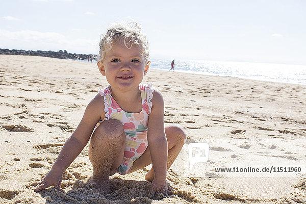 Kleines Mädchen spielt mit Sand am Strand
