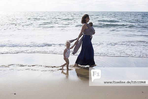 Mutter und Kinder beim Spaziergang am Strand