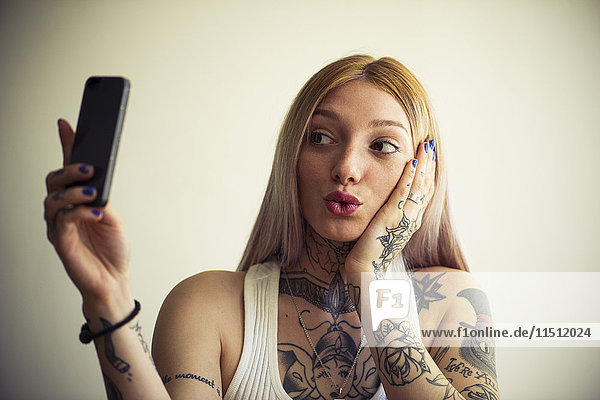 Tätowierte Frau nimmt Selfie mit Smartphone