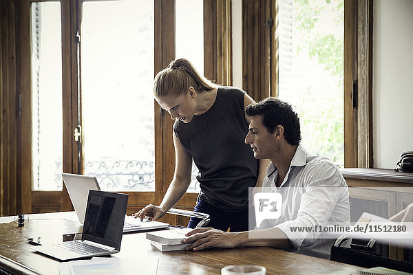 Kollegen  die gemeinsam am Laptop im Büro arbeiten